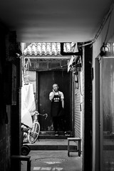 Isolation (Go-tea 郭天) Tags: qingdao man alone lonely young cook uniform bold busy duty work working job business phone mobile cell cellular cellphone network data connected connexion people talk talking discussion discuss discussing conversation private privacy narrow alley candid portrait canon eos 100d 50mm prime street urban city outside outdoor bw bnw black white blackwhite blackandwhite monochrome naturallight natural light asia asian china chinese shandong bike door chairs bicycle