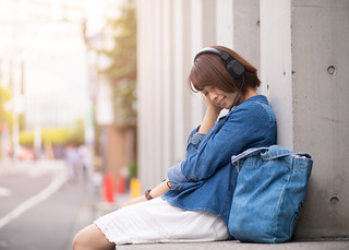 Happy young woman listening to music in city
