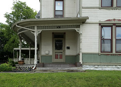 Porch — Urbana, Ohio (Pythaglio) Tags: house dwelling residence historic urbana ohio champaign county twostory balloon frame wood siding painted green 11 windows eastlake trim paired vertical boards board porch spindlework turned posts spandrels door storm transom corner blocks latticework sidewalk grass lawn trees 1891 chp6311