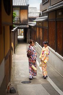 Young Kimono women looking back to us on narrow path