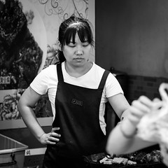 Disappointed (Go-tea 郭天) Tags: qingdaoshi shandongsheng chine cn qingdao young woman lady busy work working job duty business cook food clients customers guests eat eating tasty alone lonely disappointed surprised unexpected reaction expression wired strange candid portrait kitchen canon eos 100d 50mm prime street urban city outside outdoor people bw bnw black white blackwhite blackandwhite monochrome naturallight natural light asia asian china chinese shandong