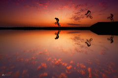 Bike night... (Kerriemeister) Tags: bike bikes reflection silhouette silhouettes composite composition water photoshop photomanipulation digital digitalart sky clouds colour colourful bmx jump sunrise