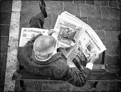 Untitled (Steve Lundqvist) Tags: people reading newspaper bench perspective pov monochrome bw giornali news prospettiva fujifilm x100s magazine reader