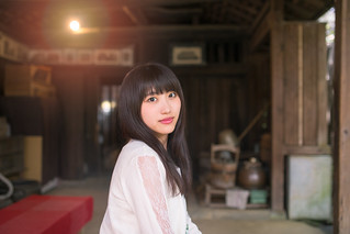 Young woman sitting on bench in old Japanese house