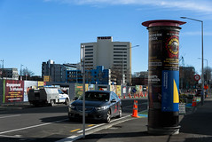 Standing Tall (Jocey K) Tags: southisland newzealand nikond750 christchurch architecture buildings bollard posters roadcones streetart mural signs street road shadows sky cars clouds