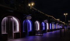 Arches at night (sussexscorpio) Tags: southcoast europe coast england uk city urban arches architecture beach brighton building eastsussex hove lights seafront sussex blue colour dusk landscape light night purple pink color reflection longexposure le promenade canon canon80d shops arch starburst signs posts lamps lamplight repeating patterns converging lines