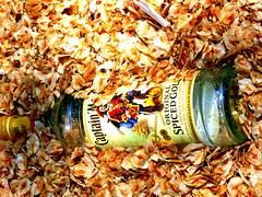 Buried in Seeds (Quetzalcoatl002) Tags: bottle captainmorgan liquor street closeup seeds buried
