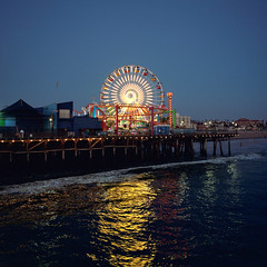 santa monica pier at dusk. 2016. (eyetwist) Tags: eyetwistkevinballuff eyetwist night ferriswheel lines santamonica pier mamiya 6mf 50mm kodak portra 400 mamiya6mf mamiya50mmf4 kodakportra400 ishootfilm ishootkodak analog analogue film emulsion square 6x6 mediumformat 120 filmexif iconla recentlyprocessedfilm epsonv750 lenstagger losangeles la angeleno california santa monica pacificocean west coast socal los angeles symmetry santamonicapier light points summer amusement park architecture structure ferris wheel ride led blue pacificpark rides wharf spokes hub purple thrill heights geometric graphic water waves reflection spiral dusk