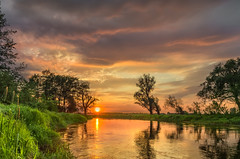 Spring changes (piotrekfil) Tags: nature landscape sunset sun river water reflections riverside clouds sky spring pentax poland piotrfil