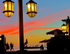 Red Sky over Red Sea (WorldExplorations) Tags: turquoise blue clouds pinkclouds light hanginglights streetlights lights lantern ship sky sunset night bay talabay arabia levant middleeast jordan resort coastline coast beach sea redsea gulf gulfofaqaba aqaba