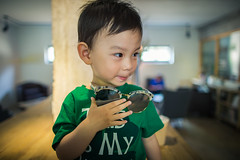Toddler smiling and holding a pair of sunglasses (HIKARU Pan) Tags: asia china portrait shanghai babyboy babyclothing blackeye blackhair carefree cheerful child childhood curiosity cute enjoyment exploration frontview handsome happiness horizontal indoors innocence joy partof person photography playful simpleliving smiling sunglasses 24l canonef24mmf14liiusm 1dx eos1dx canon