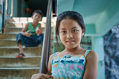 Little Cambodian girl in the stairs, White Building, Phnom Penh, Cambodia (Alex_Saurel) Tags: group detail culture portray edifice orientation asia architecture photoreport fullbody posing day reportage travel portraiture people photospecs escalier planitalien portrait building imagetype stairs vertical planpied fullframe cambodge child lifestyles photojournalism archicategory scans pose pleinformat stockcategories type time photoreportage sony50mmf14sal50f14