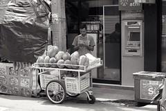 Alone with his Durian (jcbkk1956) Tags: street thonglo bangkok thailand mono blackwhite durian fruit stall streetfood vendor streetvendor thai man phone atm fuji xt1 pentax 50mmf17 manualfocus cart worldtrekker
