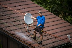 on the roof (tamapix) Tags: roof dach man mann hochdruckreiniger pressure washer tile top blue kärcher eos 7d ef 300mm f4 l is usm kenko extender canon urban neighbor area dachziegel ziegel rope seil bergsteiger climbing satellite dish antenne satellitenschüssel 14 mc4 dgx