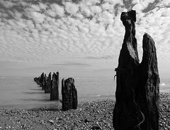Winchelsea Beach (cngphotographic) Tags: beach wooden groynes decay decayed seaside seashore water waves peddles outside outdoors summer summertime england britain eastsussex winchelsea winchelseabeach clouds sky blackandwhite monochrome gimp opensource linux fujifilm hs50exr finepix shoreline tide weathered uk shadows