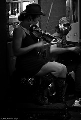 Hey, diddle diddle the cat and the fiddle. (Neil. Moralee) Tags: neilmoralee usa2017neilmoralee new orleans usa street candid musician music woman lady girl fiddle violin instrument hat window dark group people neil moralee nikon d7200 high iso bow play black white mono monochrome bw bandw blackandwhite dim night bourbon tunes hodown skirt short socks hot artist busker busking entertain entertainment entertainer gig band banjo legs boots knees motion blur