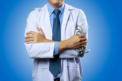 Portrait of male doctor isolated on blue  background (Krunja) Tags: adult arms asia background blue care caucasian clinic coat confident crossed doctor friendly handsome happy health healthcare healthy hospital isolated job male man mature medical medicine nurse occupation old older one people person physician portrait practitioner profession professional senior smile specialist standing stethoscope studio uniform white work young