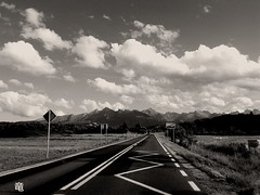 road towards the mountains =/\/\/\-- (Ola 竜) Tags: mountains landscape road asphalt stripes grass lawn mountain layers sky darkclouds perspective skyscape horizon blackandwhite monochrome monotone streetsign way whiteclouds composition urban nature