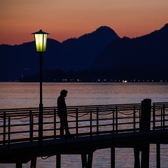 On The Bridge (CoolMcFlash) Tags: person sunset man alone evening silhouette lamp street streetphotography candid lake mountain austria sky summer bridge canon eos 60d orange light sonnenuntergang mann alleine abend kontur zwielicht twilight lampe strase see wolfgangsee gebirge berg österreich himmel sommer brücke licht fotografie photography mood stimmung tamron b008 18270 salzburg water wasser