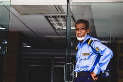 Near Agrabad as far I remember. He was a security guard of a bank. He was an aged person but looked so bold. May Allah bless him and keep him fit to do his duty!  Chittagong, Bangladesh 2015  #portrait #people #Bangladesh (Ajwad Mohimin) Tags: portrait bangladesh people security guard blue nonpro amateur