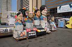 """Seoul Korea Kwanghwamun candle rally March 18 2017 empty plaza featuring whole row of effigies - """"The Gang That Couldn't Shoot Straight"""" (moreska) Tags: seoul korea kwanghwamun candle rally march 18 2017 effigy politicalart caricature satire mocking bound tiedup socialchange history protest democracy spring officials plaza afternoon outdoor nopeople sunny placard poster impeachment chaebol 광화문 capital 대한민국 rok asia"""