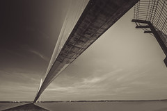 "fine art black & white perspective of Pont du Normandie arching north across the Seine River to rejoin its on shadow, nr Honfleur, Normandy, France (grumpybaldprof) Tags: canon 70d ""canon70d"" sigma 1020 1020mm f456 ""sigma1020mmf456dchsm"" wideangle ultrawide noiretblanc ""blackandwhite"" ""blackwhite"" monochrome bw fineart honfleur normandy normandie france calvados ""pontdenormandie"" bridge amazing huge impressive ""longestuntil2004"" ""bridgeofnormandy""""cablestayed"" ""cablestayedroadbridge"" ""lehavre"" ""seine ""riverseine"" ""laseine"" ""michelvirlogeux"" ""normanfoster"" river piers cables road traffic sky ocean altantic rock concrete patters lines angles vanishingpoint shadow"