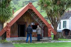 The Whaakata (Meeting House) (Jocey K) Tags: newzealand nikond750 southisland bankspenisnsula spring maoricolonialmuseumokainsbay museum landsape sky clouds mist hills building architecture people cabbagetrees meetinghouse whaakata maoricarvings cottages okainsbay
