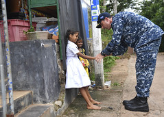 Capt. Darren McPherson gives Sri Lankan children a low-five.
