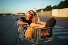 evening on a parking deck (Michael Kremsler) Tags: shooting model girl portrait fashion streetfashion sneakers allblack hotpants shirt sunglasses blond carpark parkingdeck shoppingcart bokeh city evening summer availablelight concrete midowatches