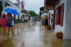 Rainy Day in St Augustine, Florida (` Toshio ') Tags: toshio staugustine florida oldtown city town street people rain raining america usa shop store flags girls fujixe2 xe2 icecream umbrella tourist tourism