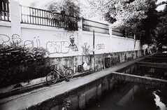 Thong Lo - Bangkok (35mm) (jcbkk1956) Tags: bangkok thailand thonglo street mono blackwhite khlong wall graffiti bicycle bike film 35mm ilford ilfordpan100 manualfocus manualexposure analog 20mmf4 nikkor worldtrekker