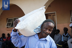 A man holding the Islamic Relief Ramadan food parcel over his shoulder in Zimbabwe