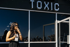 Toxic Girl 76/156 (markfly1) Tags: toxic girl smoking cigarette outside blue glass street candid juxtaposition open door reflections seafront brighton england uk funny humpur d750 35mm manual focus lens colour color