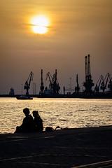Watching the sunset (Yannis_K) Tags: nikond7100 nikon70300mmf4556vr yannisk thessaloniki port sunset streetphotography sea cranes silhouette man woman cityscape city greece