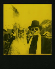 Yellow Muertos Couple (tobysx70) Tags: the impossible project tip polaroid slr680 frankenroid sx70 door rollers red black blackandred duochrome film for 600 type cameras instant blackframe impossaroid yellow couple dia de los muertos celebration hollywood forever cemetery santa monica blvd boulevard angeles la california ca man woman lady skull makeup wings hat route rte rt 66 digitally manipulated toby hancock photography
