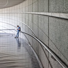 Online on Lines (Paul Brouns) Tags: paulbrouns paulbrounscom paul brouns architecture architectuur architektur perspective corridor lines light square waiting mobile phone checking man leaning