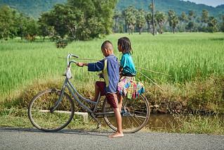 Cambodian girl and boy on bicycle, Kompong Chhnang, Cambodia