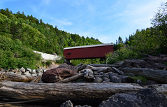 Point Wolfe Covered Bridge (TheNovaScotian1991) Tags: pointwolfe coveredbridge newbrunswick canada fallentree rocks boulders bluesky fundynationalpark appalachianmountains landscape nikond3200 tokina1116mmdxii cliffs grass hillsideforest barricade clouds ultrawideangle albertcounty