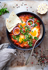 Shakshuka with pita bread (vladimirisrael) Tags: shakshuka shakshouka fried egg middleeastern israeli breakfast arab libyan egyptian tunisian algerian moroccan african traditional cuisine topview fromabove rustic vintage table vegetarian vegetable vegan tomato bellpepper sunnysideup sauce herb matbucha restaurant homemade comfort red green yellow pan garlic appetizer hipster lunch dinner healthy poached frittata cooking morning