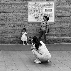 Just shoot (Go-tea 郭天) Tags: beijing hutong gulou old traditional history historical historic time past day candid portrait ancient cellular cellphone cell phone mobile camera photo photography young girl kid child daughter mother together women family cute beautiful shoot shooting capture capturing pose posing wall bricks dress drinks glass straw tourist hold hodling street urban city outside outdoor people bw bnw black white blackwhite blackandwhite monochrome naturallight natural light asia asian china chinese canon eos 100d 24mm prime