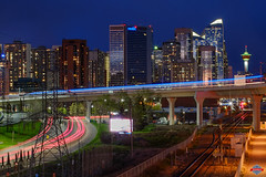 Train Lights (Rob Moses) Tags: calgary alberta canada yyc city urban metro downtown skyline sky buildings architecture citylife modern beautiful pretty uptown condos night lights apartments windows skyscrapers skyscraper nightlife explore bigcity innercity river bowriver bridge prime longexposure fujifilm xe1 50mm12 canonfd photography train subway ctrain transit
