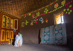 Gurage woman inside her traditional house decorated with doilies on the walls, Gurage Zone, Butajira, Ethiopia (Eric Lafforgue) Tags: abyssinia adult africa architecture art butajira clothing culture decorated decoration depiction developingcountry doily eastafrica ethiopia ethiopia0617413 ethnic fulllenght gurage homeinterior horizontal hornofafrica house hut indigenousculture indoors lowangleview onematurewomanonly onepersononly onewomanonly orthodox poverty realpeople ruralscene toukoul traditional tukul guragezone et