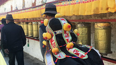 Tibet · Lhasa · Pilgrim (yoomeilleure) Tags: hair hat sacred tibet religion people street colors orange gold buddha