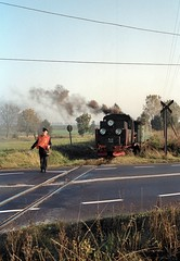 PKP Sroda variety  |  1996 by keithwilde152 - The regular train guard has cautiously appeared to halt traffic while another of the crew inspects loco Px48-1920. The Poznan-Jarocin-Lodz highway passes by Sroda's town limits about to be crossed by the 09.07 Sroda Miasto-Zaniemysl passenger. The guard's appearance is quite fleeting, generally re-boarding before negotiating the crossing. 15th October 1996