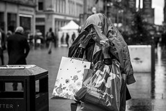 The Shopping Expedition (Leanne Boulton) Tags: monochrome people urban street candid portrait portraiture streetphotography candidstreetphotography candidportrait streetportrait eyecontact candideyecontact streetlife woman female girl face facial expression look emotion feeling mobile phone shopping bags consumerism spending wet weather rain raining shelter tone texture detail depthoffield bokeh naturallight outdoor light shade shadow city scene human life living humanity society culture canon canon5d 5dmarkiii 70mm character ef2470mmf28liiusm black white blackwhite bw mono blackandwhite glasgow scotland uk
