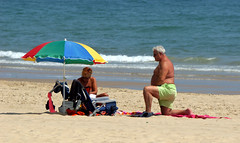 """What do you mean, you've got to phone a friend?"" (SteveJM2009) Tags: candid beach couple imagined sunshade umbrella proposal branksome dorset uk june 2017 heatwave stevemaskell"