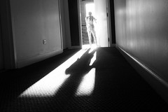 let it in (KevinIrvineChi) Tags: doorway light lateafternoon sunlight sun sunny bnw bw blackwhite blackandwhite noir blanc black white monochrome hallway apartmentbuilding interior indoors stairwell carpet texture textured girl standing door walls outlet sony dscrx100