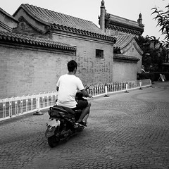 Young and ancient (Go-tea 郭天) Tags: pékin beijingshi chine cn beijing hutong gulou ancient road pavement old tradition traditional history historical historic buidling house construction candid motorbike motorcycle man young alone ride ridding rider back backside lonely fast movement transportation transport roof day wall empty place street urban city outside outdoor people bw bnw black white blackwhite blackandwhite monochrome naturallight natural light asia asian china chinese canon eos 100d 24mm prime local