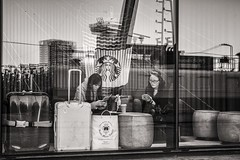 in transit (Gerard Koopen) Tags: nederland netherlands amsterdam city capital candid straat street straatfotografie streetphotography reflections luggage tourists intransit bw blackandwhite blackandwhiteonly waiting coffee koffie bagage centraalstation centralstation starbucks fujifilm fuji xpro2 35mm 2016 gerardkoopen