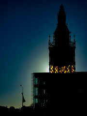 The Winter Sun Rises (Steve Taylor (Photography)) Tags: art architecture building lamppost black blue green yellow orange newzealand nz southisland canterbury christchurch city winter sun sunshine dawn sunrise diamondjubilee heritage leadedlights stainedglass thevictoriaclocktower tower